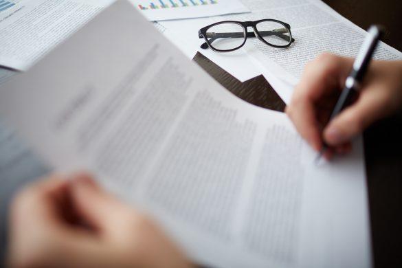 Individuo analisando o edital de licitação
